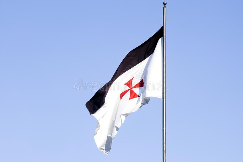 Templar flag. Templar stronghold at Jerez de los Caballeros, Spain. Detail of flag over blue sky stock photography