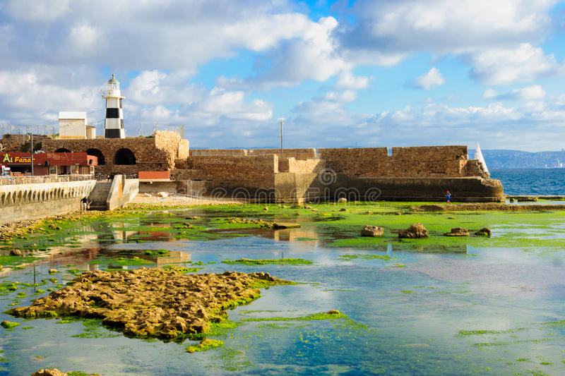 Templar Fortress in Acre. ACRE, ISRAEL - MAY 04, 2015: Scene of a Templar Fortress remains, lighthouse, restaurants, local fishermen and Haifa bay, in the old royalty free stock photo