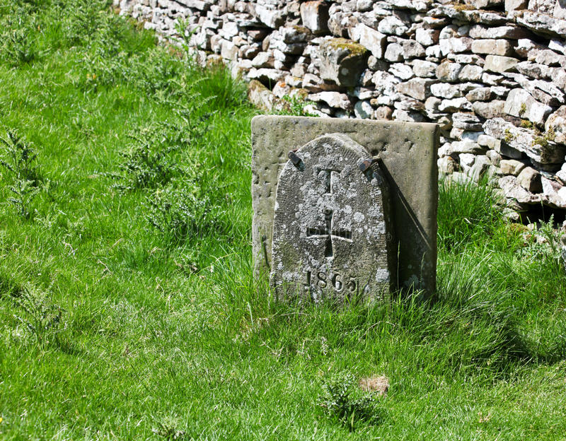 Templar Marker. A limestone tablet by a stone fence in the English countryside marks a cemetery entrance for the Knights Templar crossed dated 1865 royalty free stock photos