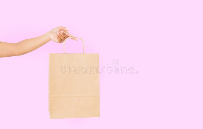 Template blank package. African american woman hand holding a paper kraft bag on pink background. Delivery and shopping royalty free stock image