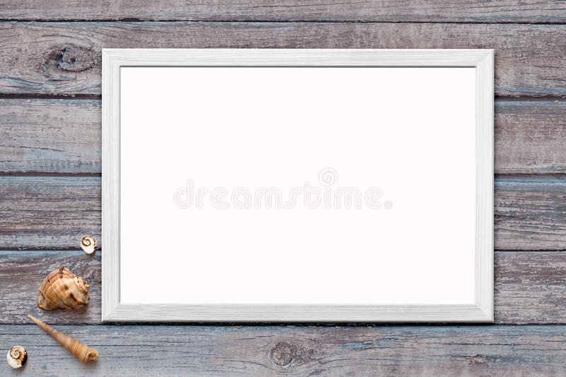 Template of blank poster in wooden frame on rustic wooden background with seashells. Mock up of blank poster in wooden frame on rustic wooden background with stock photos