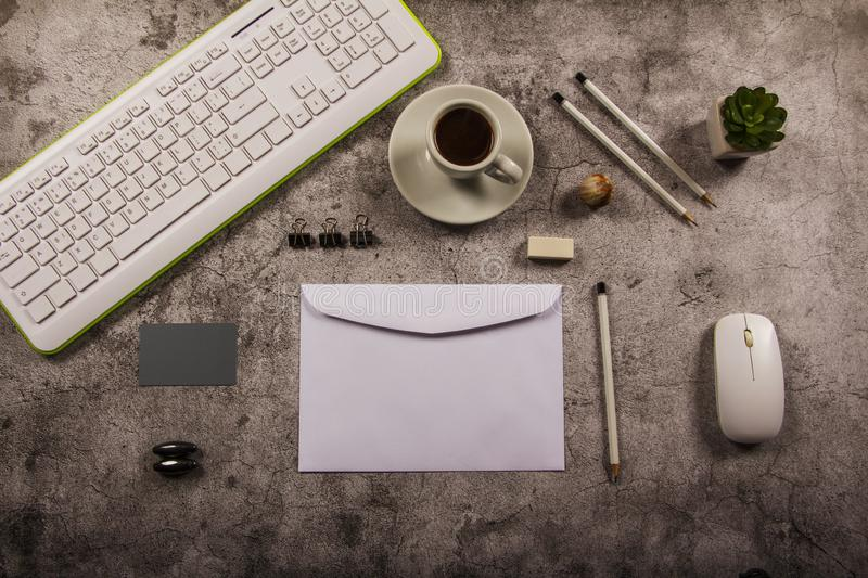 Template mock up desk mockup with computer keyboard, tablet drawing business idea empty envelope, notebook and cup of coffee in gr. Ay background. View from royalty free stock photos