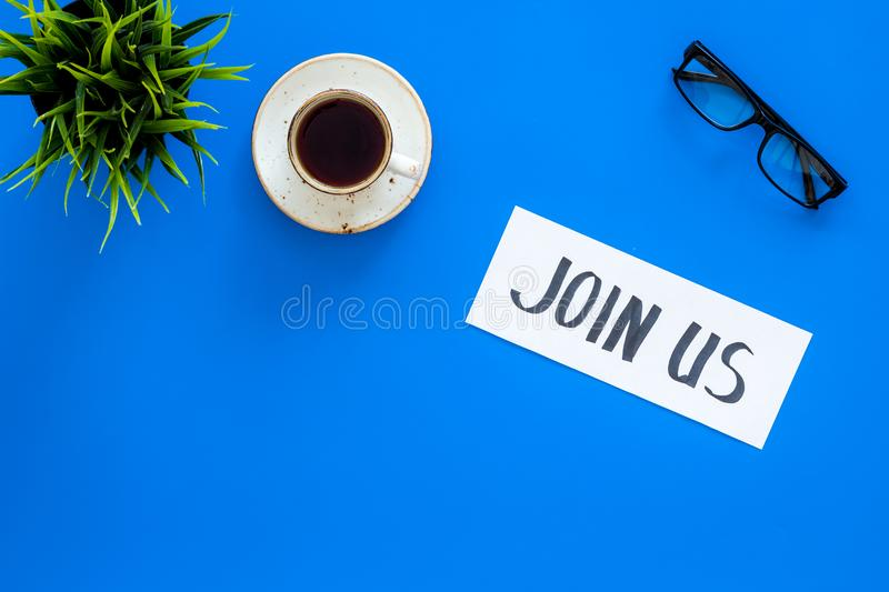 Template for socail media links. Hand lettering Join us on work desk with glasses, coffe, plant on blue background top. View stock photography