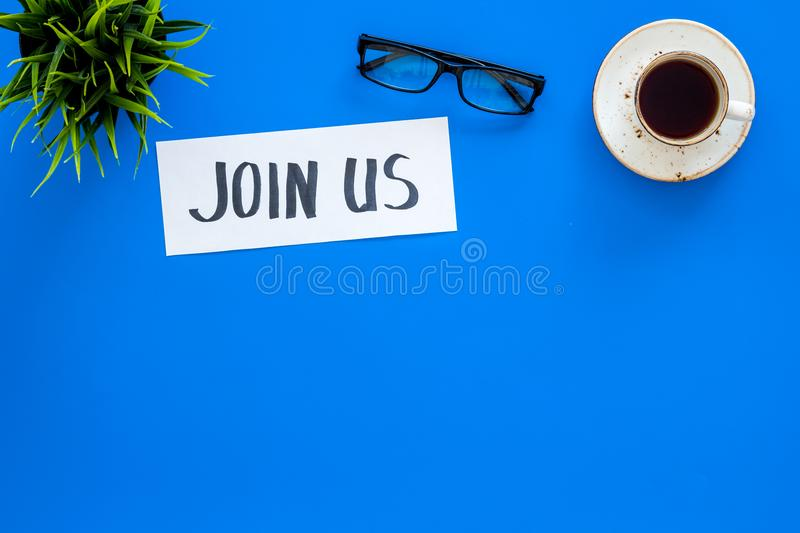 Template for socail media links. Hand lettering Join us on work desk with glasses, coffe, plant on blue background top. View royalty free stock image