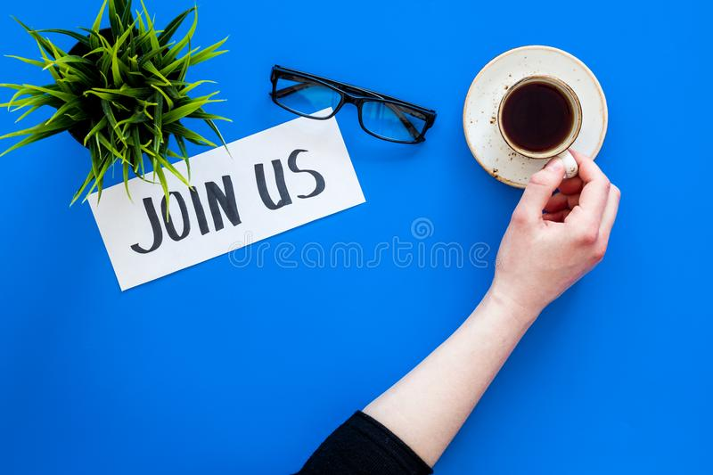 Template for socail media links. Hand lettering Join us on work desk with glasses, coffe, plant on blue background top. View royalty free stock images