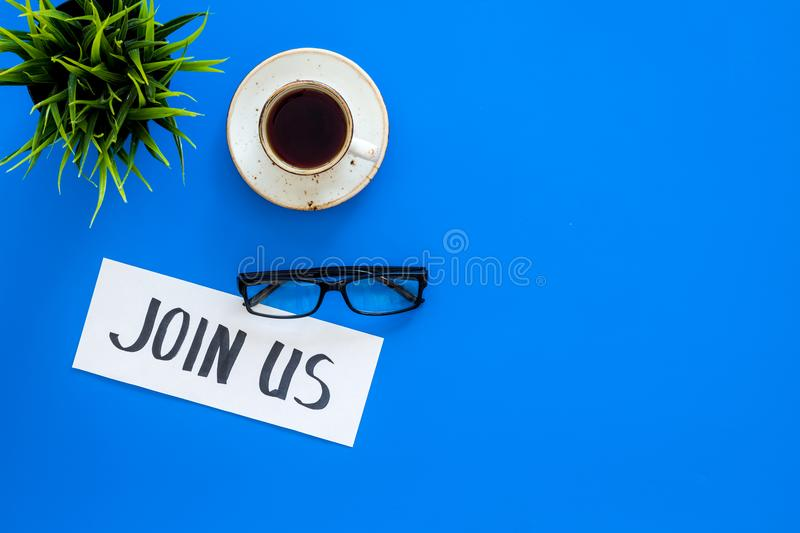 Template for socail media links. Hand lettering Join us on work desk with glasses, coffe, plant on blue background top. View royalty free stock photo