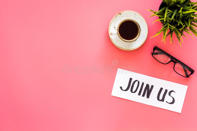 Template for socail media links. Hand lettering Join us on work desk with glasses, coffe, plant on pink background top. View royalty free stock photo