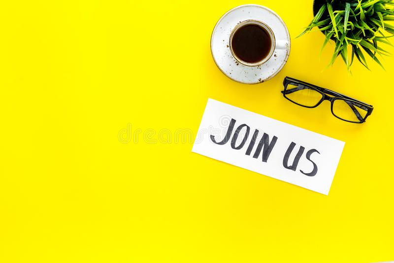 Template for socail media links. Hand lettering Join us on work desk with glasses, coffe, plant on yellow background top. View royalty free stock photos
