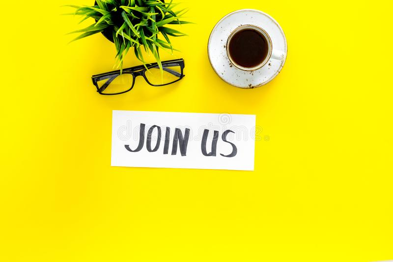 Template for socail media links. Hand lettering Join us on work desk with glasses, coffe, plant on yellow background top. View royalty free stock images