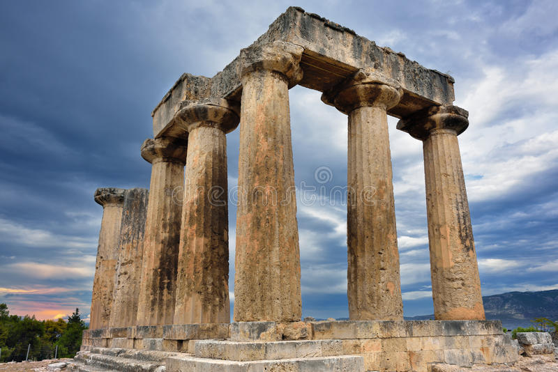 Temple of Apollo in Ancient Corinth Greece. Colonnade of the Temple of Apollo under dramatic cloudy sky at sunset in Ancient Corinth. Greece stock images