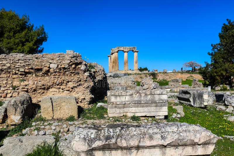 Temple of Apollo in ancient Corinth Greece viewed from down the hll in the excavated ruins with unidentifiable tourists taking pic stock photo