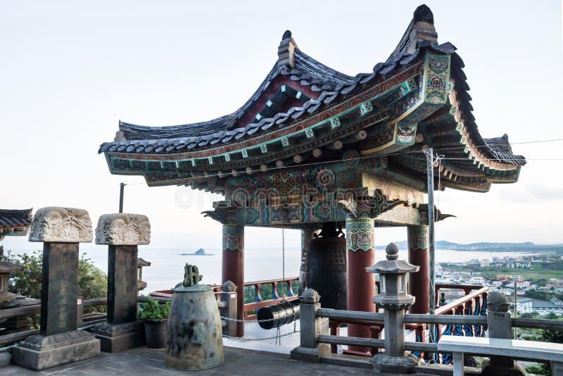 Temple bell house with view over coastline at Sanbanggulsa temple, Sanbang-ro, Jeju Island, South Korea stock photos