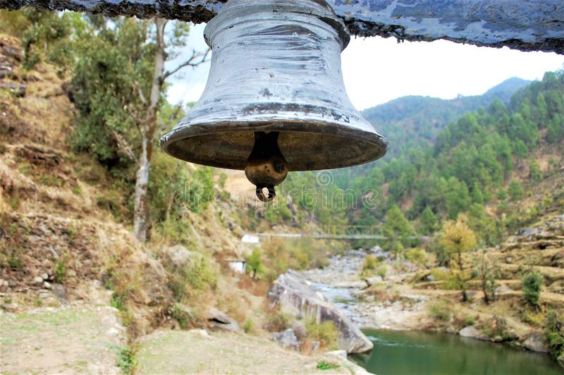Temple Bell with river background. Temple bell showing beauty of human creativity and presenting peaceful message royalty free stock image