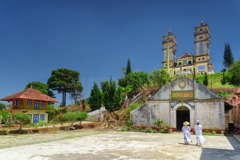 Temple for the Cao Dai religion adherents at Dalat, Vietnam. Towers of the Thanh That Da Phuoc on blue sky background. Scenic view of the temple for the Cao Dai stock photo