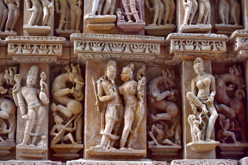 Temple carvings. Idols of gods and goddesses carved out on the walls of 11th century Khajuraho temples of India stock image