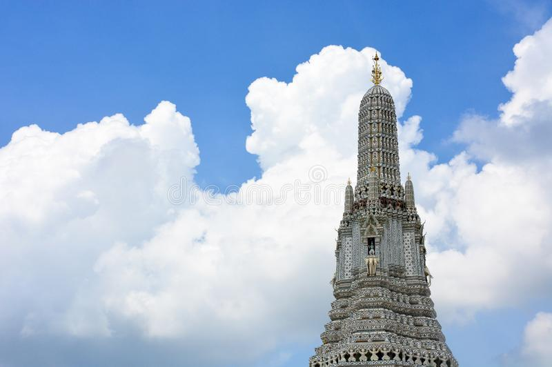 The Temple of Dawn or Wat Arun Buddhist temple with a beautiful blue sky and clouds background, copy space. This place is a popular travel destination among stock photos