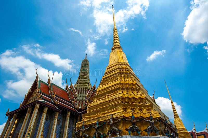 Temple and golden pagoda on blue sky at Wat Phra Kaew royalty free stock photos