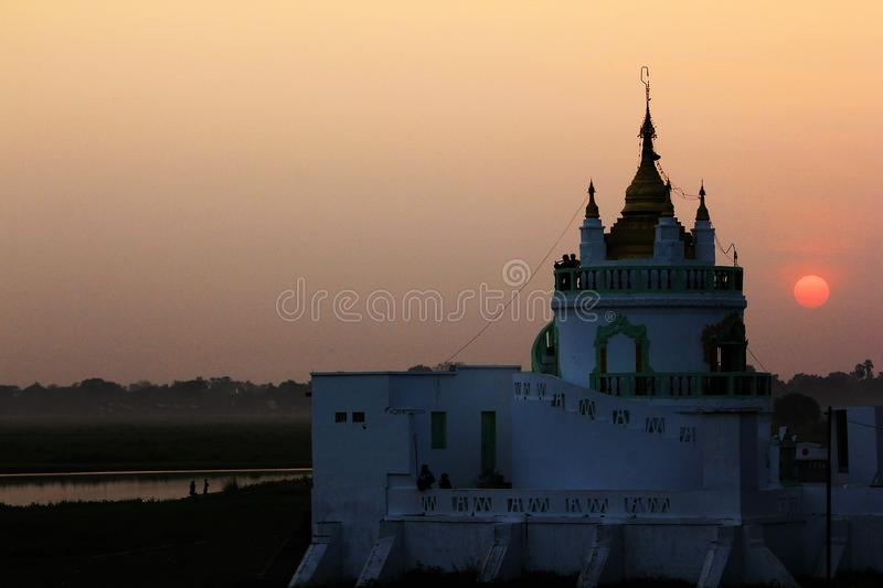 The temple has white and sunset in Myanmar. stock photo
