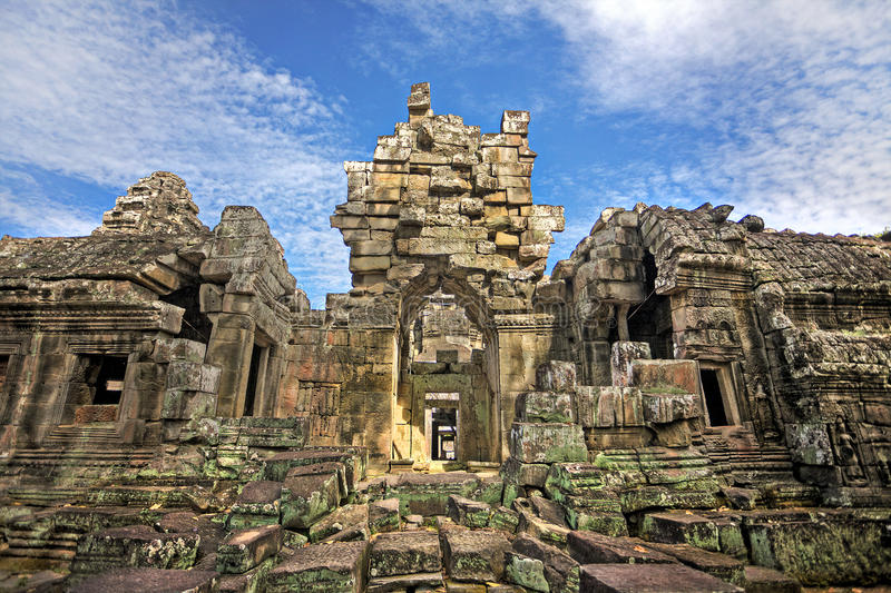 Temple ruins. Cambodian temple ruins turning to rubble, blue sky background stock images
