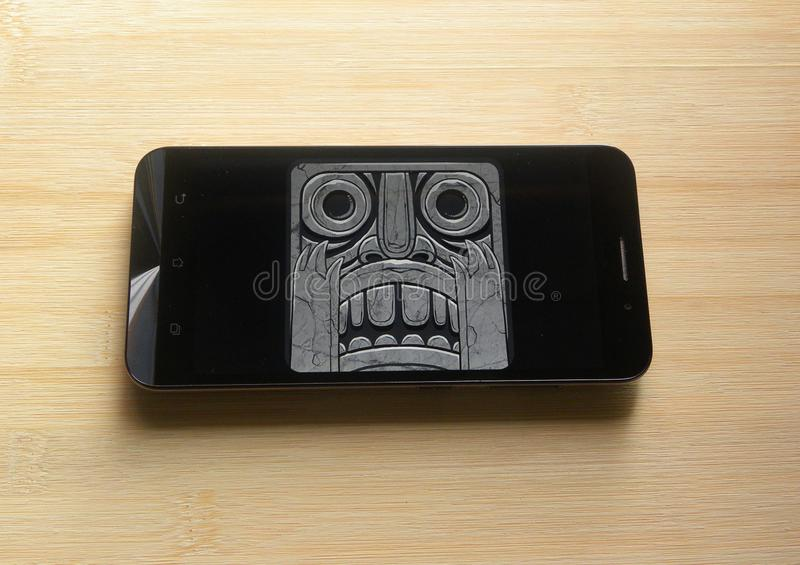 Temple Run 2 game app. On smartphone kept on wooden table stock images