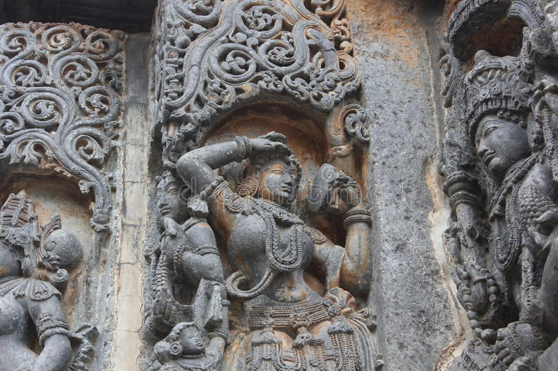 Hoysaleswara Temple wall carved with sculpture of Darpana Sundari beautiful lady with mirror. This is a temple wall carved with sculpture of Darpana Sundari stock photo
