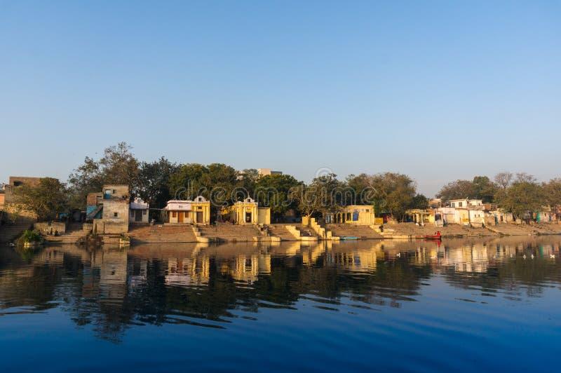 Temples jaunes et bâtiments reflétés en rivière de yamuna au ghat à Delhi photos libres de droits
