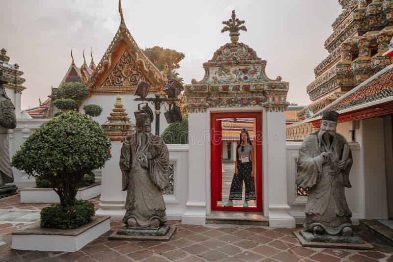 Templo asiático fabuloso, místico, budista A mulher é imprimida pela beleza das estátuas A menina olha foto de stock
