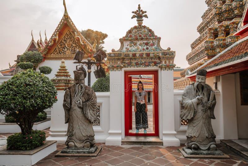 Templo asiático fabuloso, místico, budista A mulher é imprimida pela beleza das estátuas A menina olha fotografia de stock