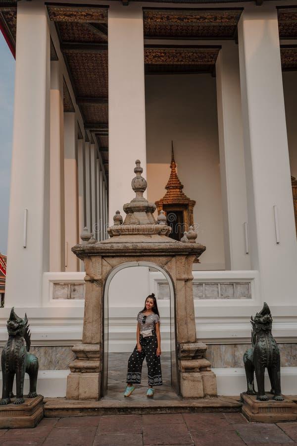 Templo asiático fabuloso, místico, budista A mulher é imprimida pela beleza das estátuas A menina olha fotografia de stock royalty free