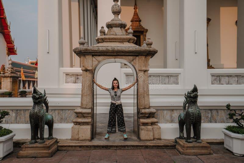 Templo asiático fabuloso, místico, budista A mulher é imprimida pela beleza das estátuas A menina olha imagem de stock
