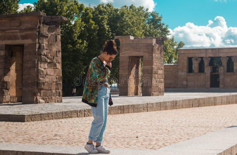 Templo de Debod, Madri ESPANHA - 10 DE JUNHO DE 2018 Mulher à moda nova com penteado ocasional do bolo que admira o monumento egí imagem de stock