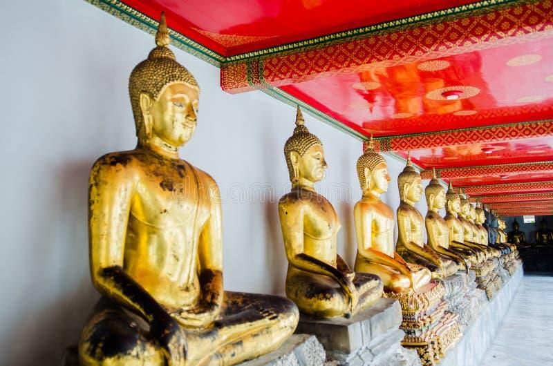 Templo de oro alineado Bangkok Tailandia de Wat Pho de las estatuas de Buda imágenes de archivo libres de regalías