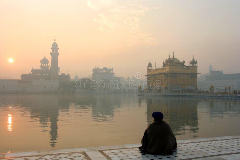 Templo de oro con un hombre en la meditación foto de archivo