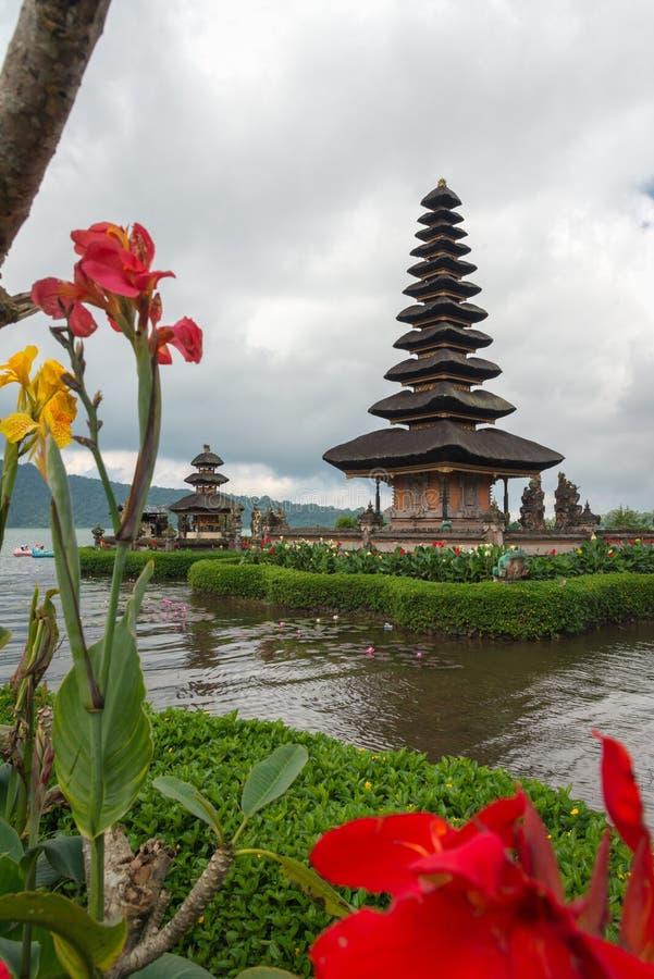Templo de Pura Ulun Danu em um lago Beratan no dia nebuloso com grama verde e primeiro plano colorido das flores em Bali, Indonés imagens de stock royalty free