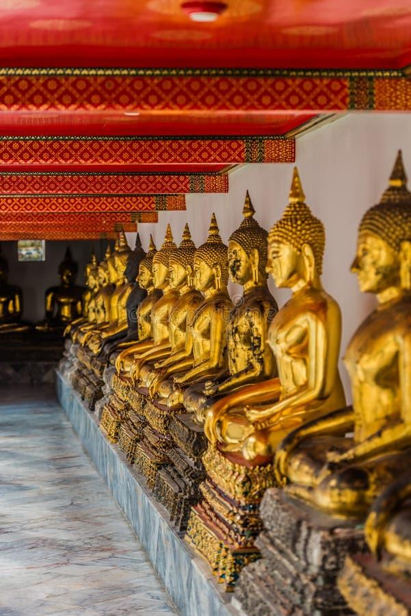 Templo dourado alinhado Banguecoque Tailândia de Wat Pho das estátuas de buddha imagem de stock royalty free