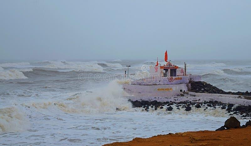Templo en una isla rodeada de olas de viento en el Océano tormenta durante el ciclón Vayu - Devbhumi Dwarka, Gujarat, India foto de archivo