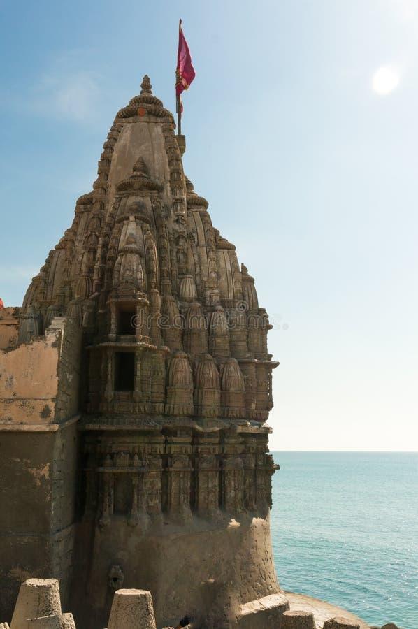 Templo hindú con las paredes talladas un altos chapitel y bandera en la costa del mar azul fotos de archivo libres de regalías