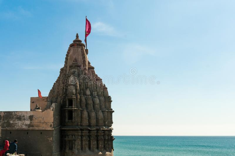 Templo hindú con las paredes talladas un altos chapitel y bandera en la costa del mar azul foto de archivo