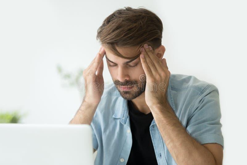 Templos conmovedores del hombre joven que intentan dolor de cabeza enfocarse o de la sensación fotografía de archivo libre de regalías