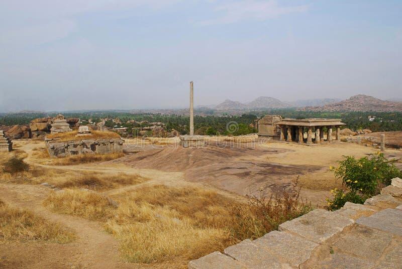 Templos no monte de Hemakuta, Hampi, Karnataka Centro sagrado Um cargo monolítico alto da lâmpada é considerado igualmente imagens de stock royalty free
