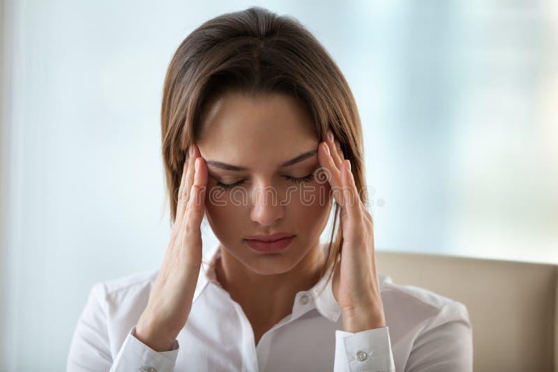 Templos tocantes da dor de cabeça ou da enxaqueca do sentimento da mulher para aliviar p foto de stock