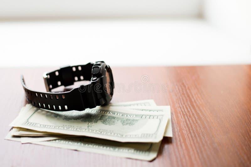 Tempo é dinheiro Cem dólares e relógio preto na tabela de madeira imagem de stock royalty free