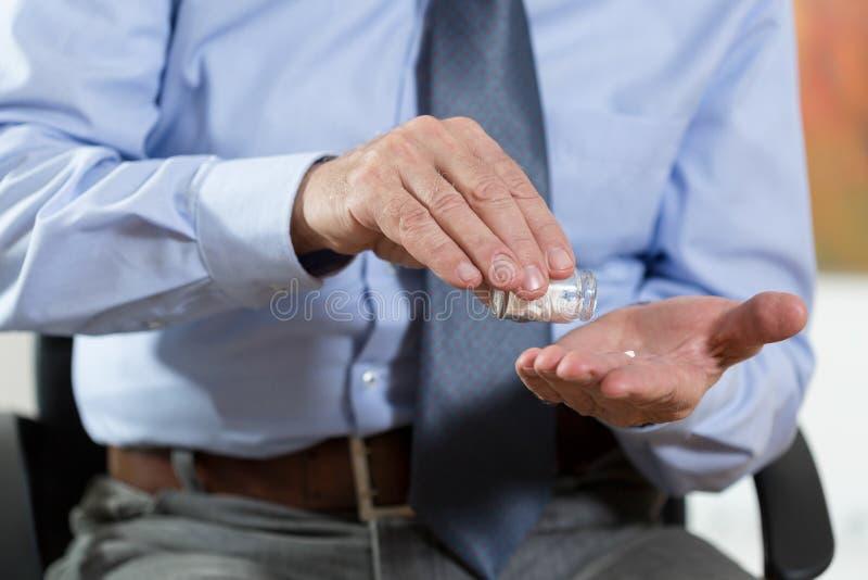 Tempo ad un farmaco per l'uomo anziano immagine stock libera da diritti