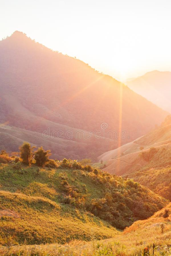 Tempo bonito Paisagem cênico brilhante e colorida A luz solar dourada brilha para baixo em torno das montanhas e dos campos de al imagens de stock