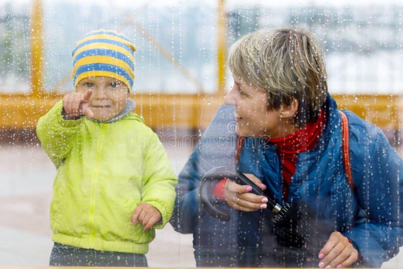 Tempo chuvoso e um rapaz pequeno com sua mãe atrás do vidro, gotas da chuva na janela imagens de stock royalty free