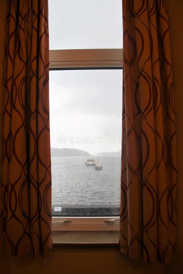 Tempo chuvoso em Escócia Vista através de uma janela na baía de Oban, Escócia imagens de stock royalty free