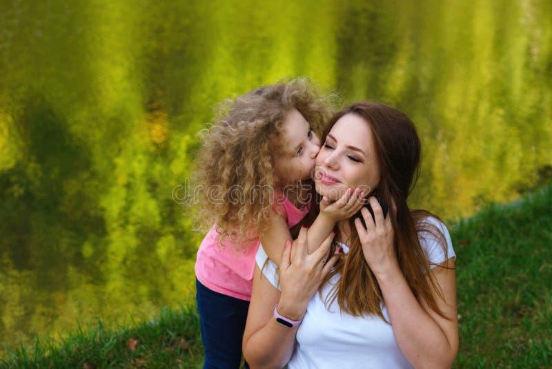 Tempo da família Mãe e filha no banco de rio A menina abraça e beija a mãe imagem de stock royalty free