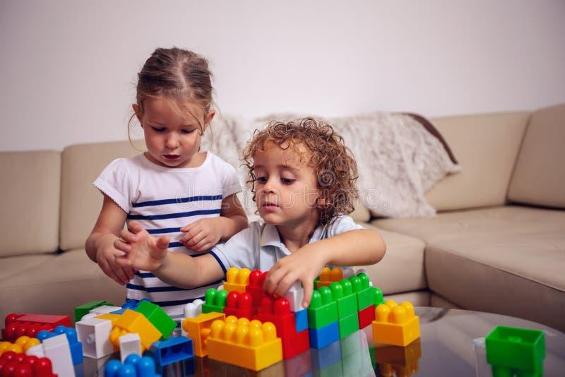 Tempo da família - menina e menino que jogam com brinquedos e que têm o toge do divertimento fotos de stock royalty free