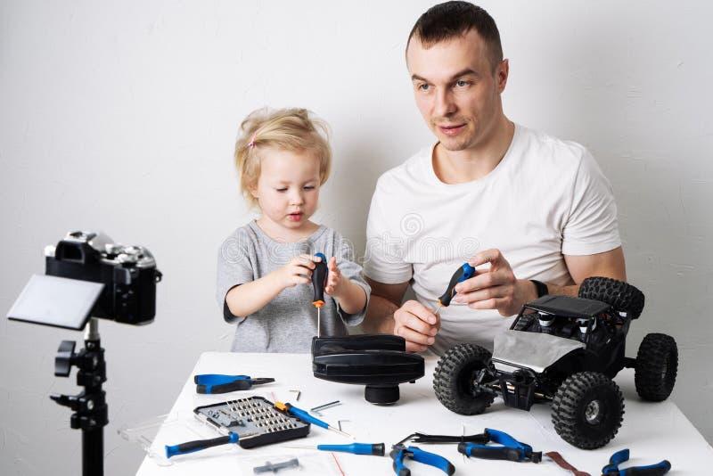 Tempo da família: O reparo do paizinho e da filha o rádio do rc controlou o modelo com erros do carro e para conduzir um blogue v foto de stock