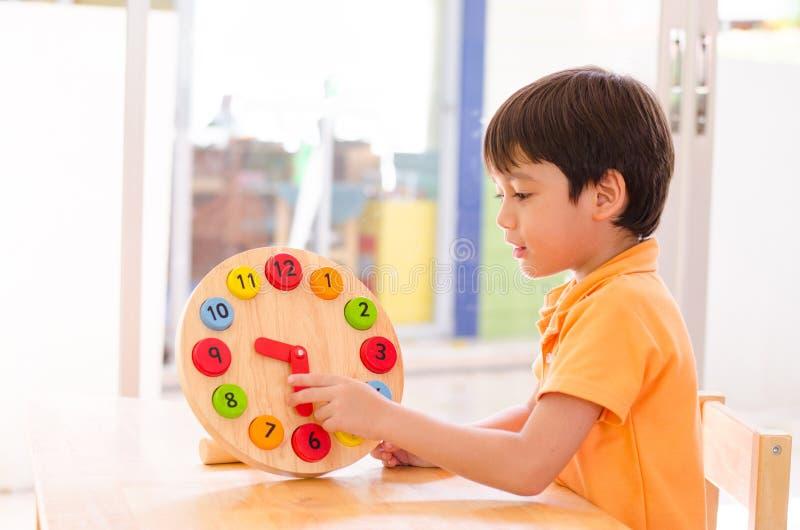 Tempo de aprendizagem do rapaz pequeno com o brinquedo do pulso de disparo do educationa do montessori imagens de stock